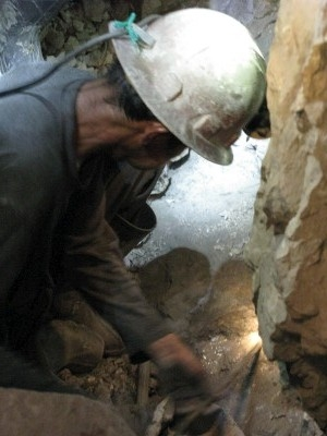 Miner drilling hole by hand for a dynamite charge