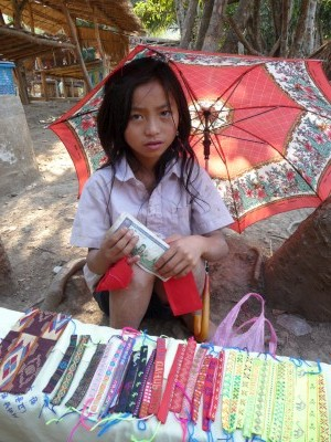 Girl selling trinkets by the road